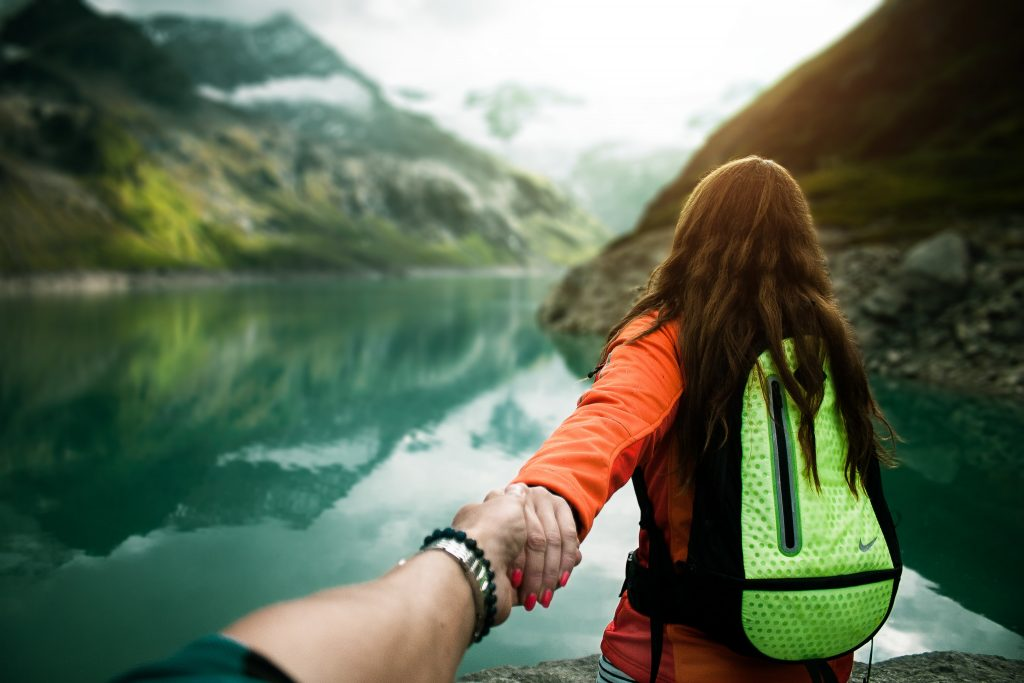 Image shows a girl on a journey carrying a backpack leading somebody by the hand
