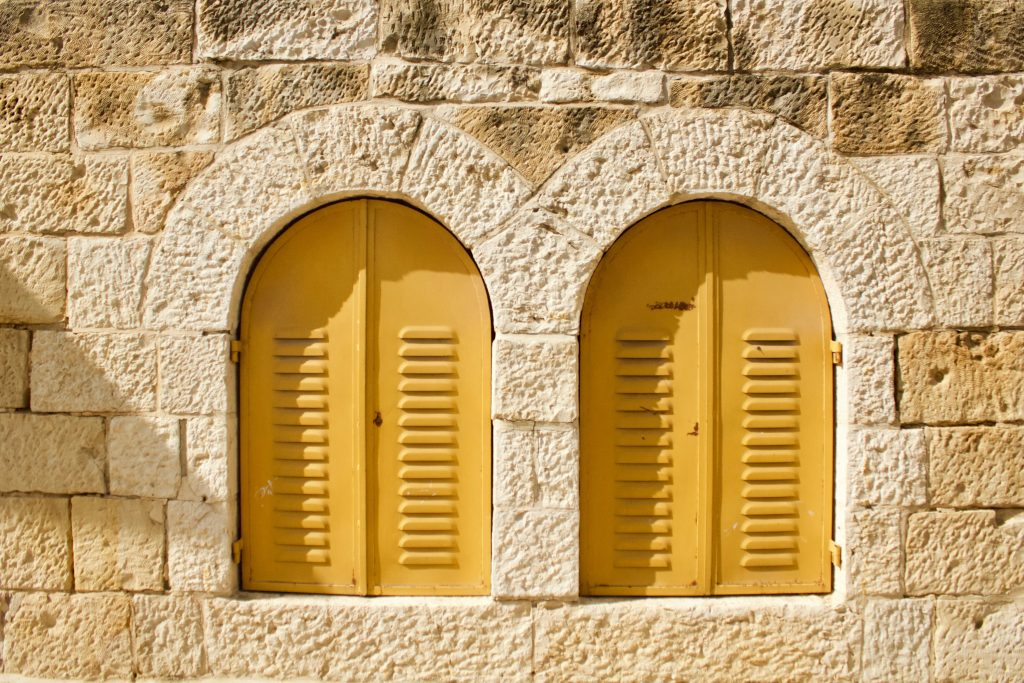 French stone wall with 2 yellow shuttered windows